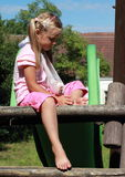 Little girl with broken hand on slide. Sad barefoot little girl with broken hand on the playground stock photography