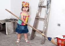 The little girl with a broom with hands Stock Photos
