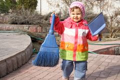 Little Girl with Broom and Trowel Outdoors. Going to Clean Stock Image