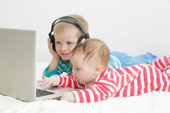 Little girl with brother looking at laptop Stock Photo
