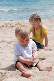 Little girl with brother sitting on the beach Stock Photos