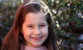 Little girl with brown hair and happy expression stock photo