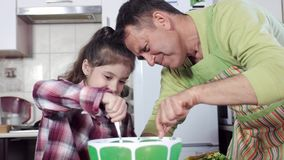 Girl with brown hair mixes products in big bowl using spoon. Little girl with brown hair mixes actively products in big green bowl using spoon under guidance of stock video footage