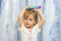 The little girl brushes the hair with a hairbrush. The little girl combs hair a hairbrush Stock Photography