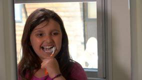Girl cleans his teeth. Little girl brushes his teeth in the bathroom stock footage