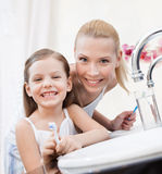 Little girl brushes teeth with her mom Stock Images