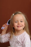 Little girl brushing hair Stock Images
