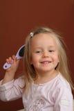 Little girl brushing hair stock images