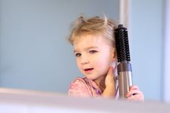 Little girl brushing her hair Stock Images