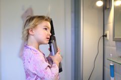 Little girl brushing her hair Stock Image