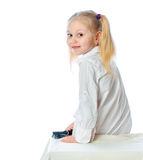 Little girl brushing her hair, white dress, on a w Royalty Free Stock Images