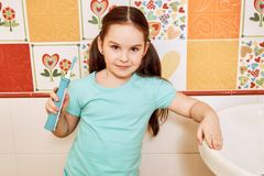 Little girl brushing her teeth in the bathroom royalty free stock photography
