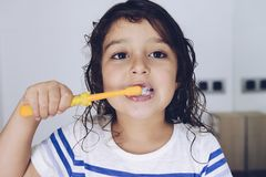 Little girl brushing her teeth before going to bed. Portrait of a little girl brushing her teeth in the bathroom before going to bed after taking a shower, kids stock photography