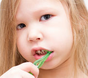 Little girl brushing her teeth with a green toothbrush Stock Images