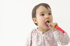 Little girl brushing her teeth isolated on white Stock Photo