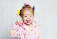 Little girl brushing her teeth. Pink brush royalty free stock photos