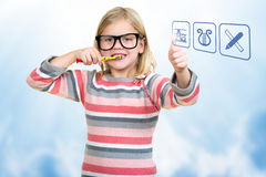 Little girl brushing her teeth with school icons. Stock Photos