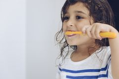 Little girl brushing her teeth after shower. Portrait of a little girl brushing her teeth in the bathroom before going to bed after shower, kids hygiene concept royalty free stock images
