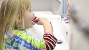 Little girl is brushing her teeth, then wiping face and hands on a towel and leaving the frame. stock video footage