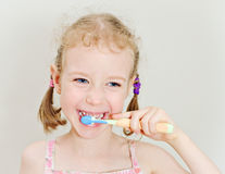 Little girl brushing her teeth. Stock Photos