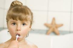 Little girl brushing teeth. In bath stock image