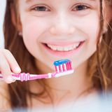 Little girl brushing teeth in bath Royalty Free Stock Images