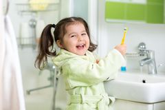Little girl brushing teeth in bath Stock Image