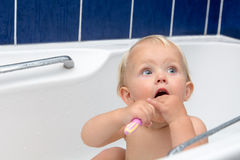 Little girl brusing teeth. Little girl is brushing teeth in bathroom in a white bathtub. Blue tiles behind Royalty Free Stock Images