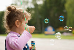Little girl and the bubbles Stock Photos