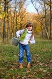 Little girl with a bucket in the autumn park Stock Photos