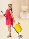 Little girl with bucket and brush cleans the house. Stock Photo