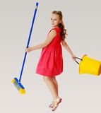 Little girl with bucket and brush cleans the house. Royalty Free Stock Photos