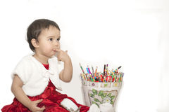 Little girl with a bucket of colored pencils. And clock Royalty Free Stock Photo