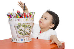 Little girl with a bucket of pencils. At table stock photography
