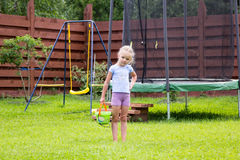 Little girl with bucket of water going to wash her trampoline Stock Photos