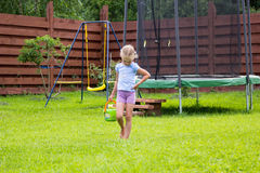 Little girl with bucket of water going to wash her trampoline Stock Photography