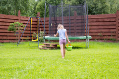 Little girl with bucket of water going to wash her trampoline Royalty Free Stock Image