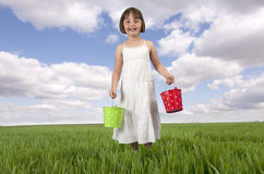 Little girl with buckets in meadow Stock Images