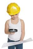 Little girl builder in yellow helmet analysing drawing through the magnifiying glass Royalty Free Stock Image