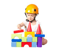 Little girl building blocks. Little girl in helmet hat building blocks on white stock photo