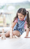 Little girl building blocks while sitting on hardwood floor Stock Photo