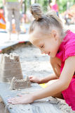 Little girl building a sand castle in the sandbox Stock Photography