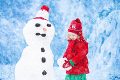 Little girl building a snow man in winter Royalty Free Stock Images