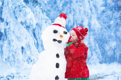 Little girl building a snow man in winter Stock Photos