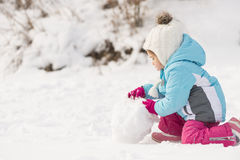 Little girl building a snowman. Funny little girl  in a warm winter outfit, building a snow man. Kid playing outdoors in winter.  Happy little kid is playing in Royalty Free Stock Photo