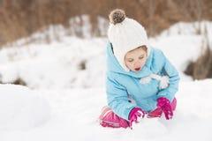 Little girl building a snowman Stock Image