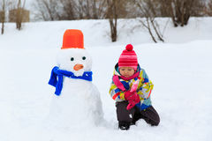 Little girl building snowman in nature Stock Photography