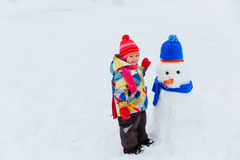 Little girl building snowman in winter nature Stock Photo
