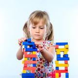 Little girl building structure with wooden blocks. Royalty Free Stock Photos