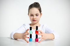 Little girl builds. A pyramid using nail polishes Stock Image